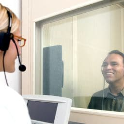 Man in a booth receiving a hearing test with a doctor on the other side of the booth