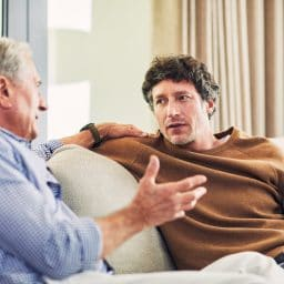 Shot of a mature man and his elderly father sitting on the sofa at home and chatting