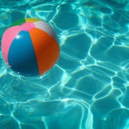 A beach ball floating inside of a swimming pool.