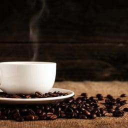 A hot cup of coffee surrounded by coffee beans.
